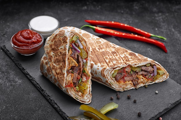 Shawarma with veal, with sauce, onions, pickles, herbs and hot red pepper, on slate, against a dark concrete background Premium Photo