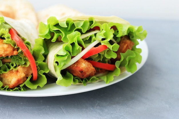 白い皿にドナーケバブ。肉、玉ねぎ、サラダ、灰色の背景上のトマトのshawarma。 Premium写真