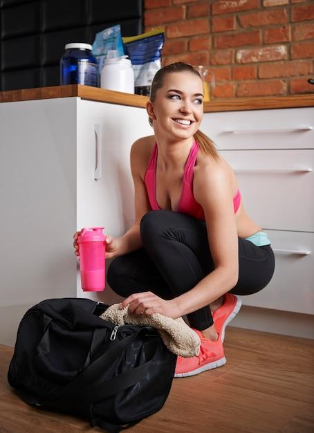 그녀는 항상 체육관 가방에 단백질 음료를 가지고 있습니다. 무료 사진