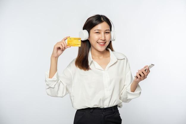 彼女は買い物に行き、クレジットカードとスマートフォンを持って行くために白いシャツと黒いズボンを着ていました 無料写真