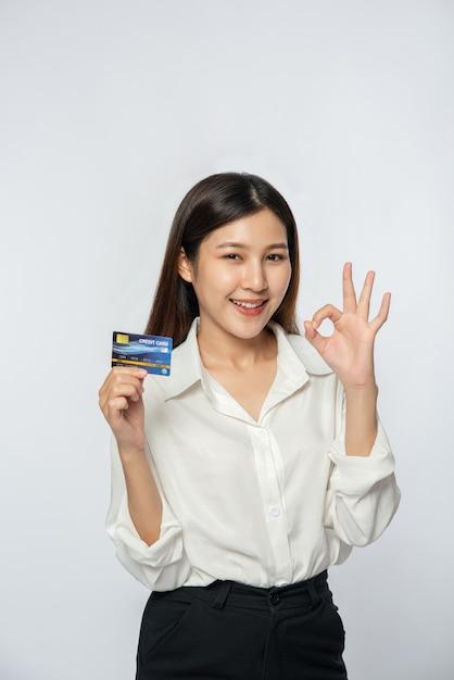 彼女は買い物に行ってクレジットカードを持っているために白いシャツと黒いズボンを着ていました 無料写真