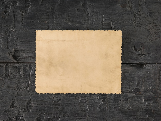 A sheet of old paper on a black wooden table. retro writing paper. flat lay the view from the top. Premium Photo