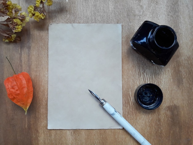 Sheet of paper, an inkwell and dry flowers Premium Photo