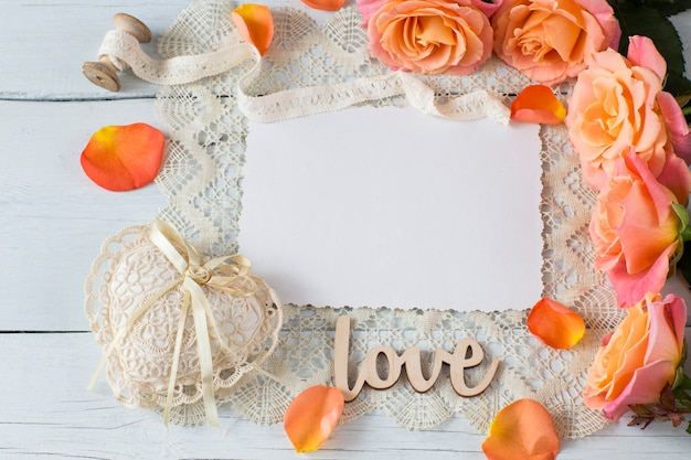 A sheet of paper, orange roses, a heart of lace, rose petals and lace Premium Photo