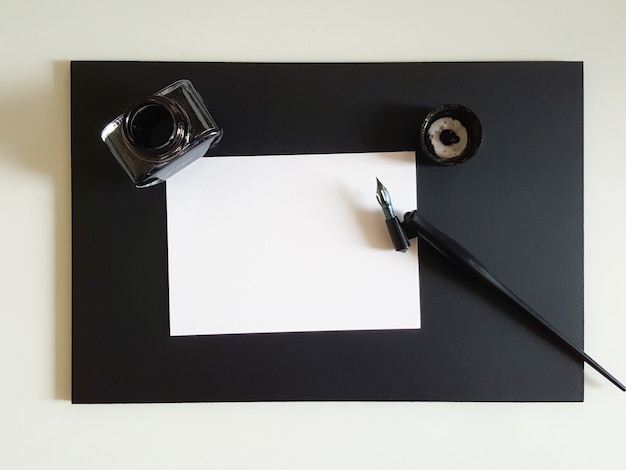 Sheet of paper, pen and ink of black on black office desk. Free Photo