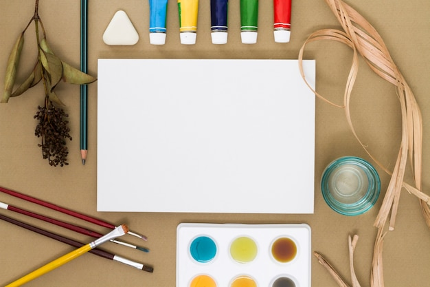 Sheet of paper surrounded by drawing supplies Free Photo