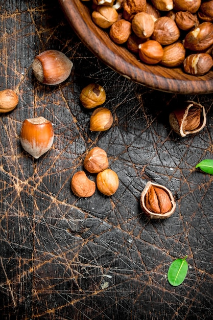 Shelled hazelnuts with leaves in a bowl . on a wooden. Premium Photo
