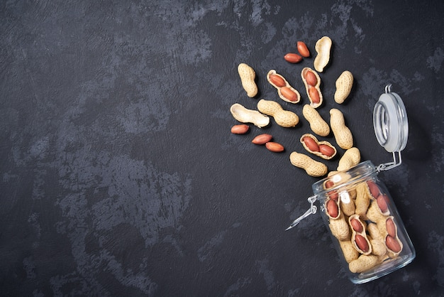Shelled and unshelled peanut in an open glass jar on black table, with copy space. top view. Premium Photo