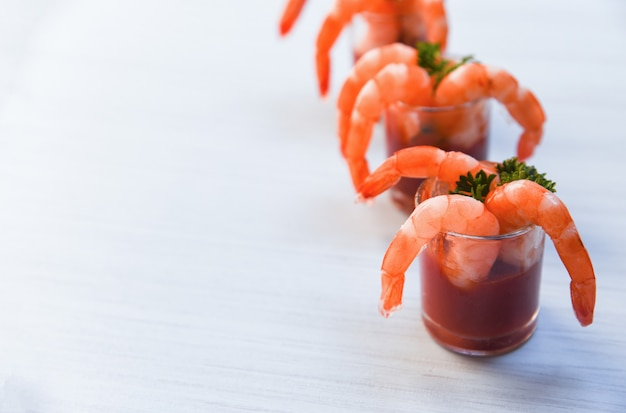 Shellfish seafood boiled shrimps prawns ketchup and spices in the dining table Premium Photo
