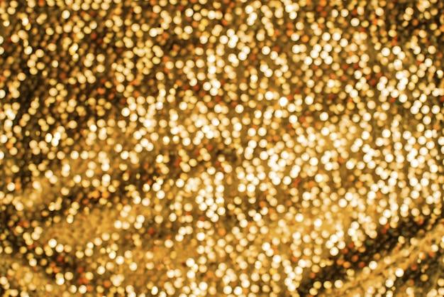 Shimmering festive background texture of shiny gold color defocus Premium Photo