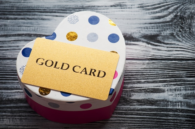 Shimmering gold card on heart shape pink box Premium Photo