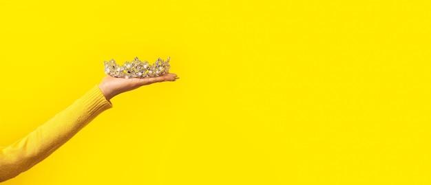 黄色の上の女性の手に輝く輝き Premium写真