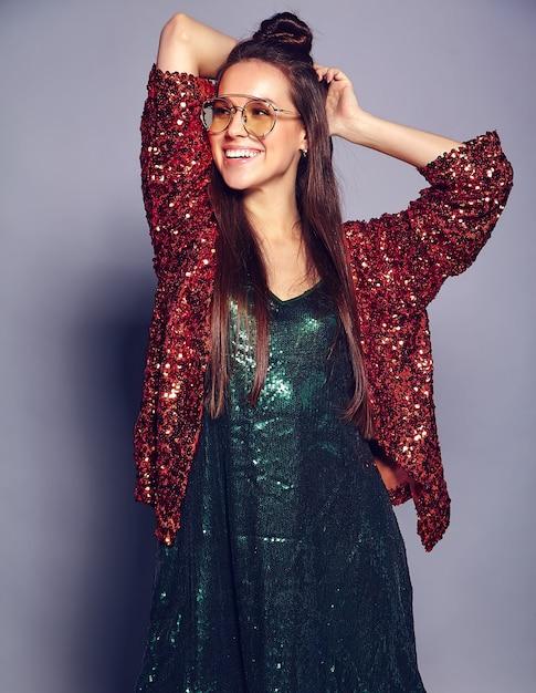 Красивая кавказская усмехаясь модель женщины брюнет битника в яркой shinny отражая стильную куртку лета и зеленое платье представляя на сером цвете Бесплатные Фотографии