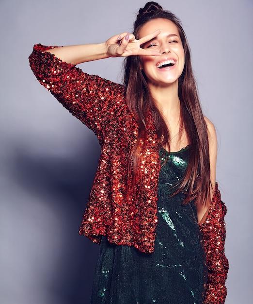 Красивая кавказская усмехаясь модель женщины брюнет битника в яркой shinny отражая куртке лета стильной и зеленом платье представляя на сером цвете. показывая знак мира Бесплатные Фотографии