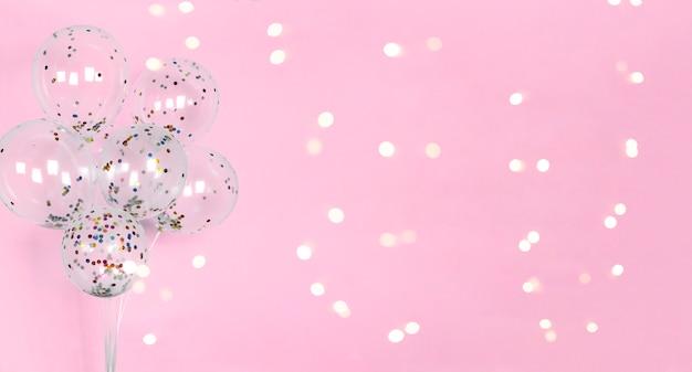 風船でお祝いのピンクの背景に光沢のあるボケライト Premium写真