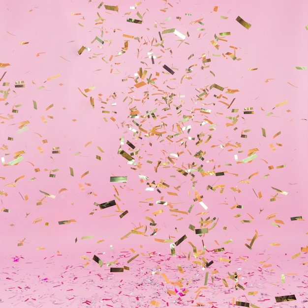 Shiny golden confetti falling on pink background Free Photo
