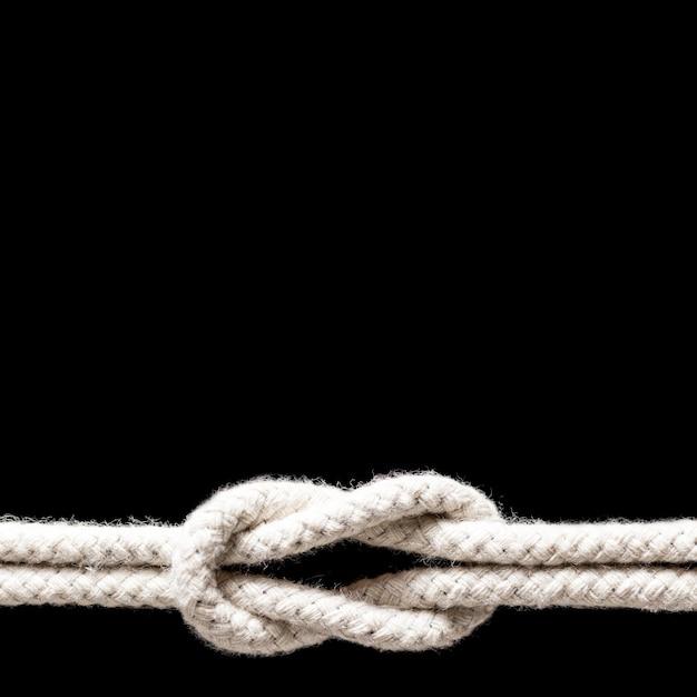 黒の背景に分離された白いロープの結び目を出荷します。 無料写真