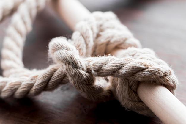 バーのクローズアップで結ばれた白いロープの結び目を出荷します。 無料写真