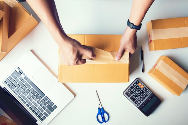 Shipment online sales .man worker delivery service and working packing box, business owner working checking order to confirm before sending customer in post.top view Premium Photo