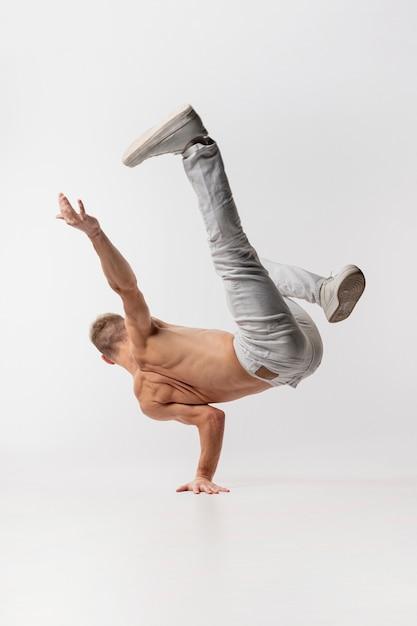 Танцор без рубашки в джинсах и кроссовках позирует во время танца Premium Фотографии