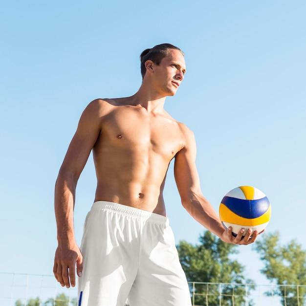 Giocatore di pallavolo maschio senza camicia che si prepara a servire la palla Foto Gratuite