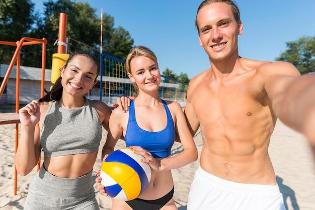 Giocatore di pallavolo maschio senza camicia che prende selfie con due giocatori di donne Foto Gratuite