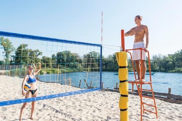 Uomo a torso nudo come arbitro di una partita di beach volley con giocatrice Foto Gratuite