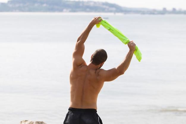Shirtless man doing side bend exercise at sea Free Photo