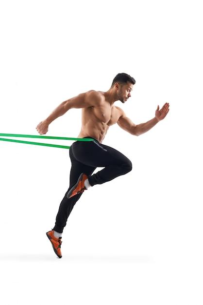 Uomo senza camicia che corre sul posto usando la fascia di resistenza. Foto Gratuite