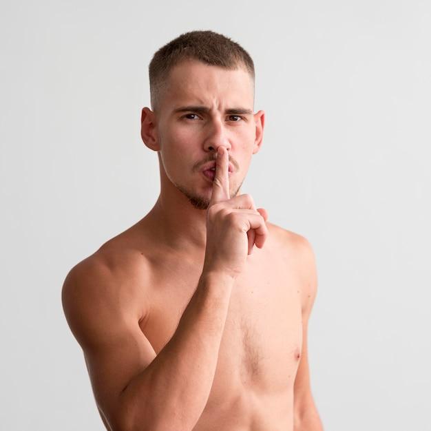 Uomo a torso nudo che ti dice di stare zitto Foto Gratuite