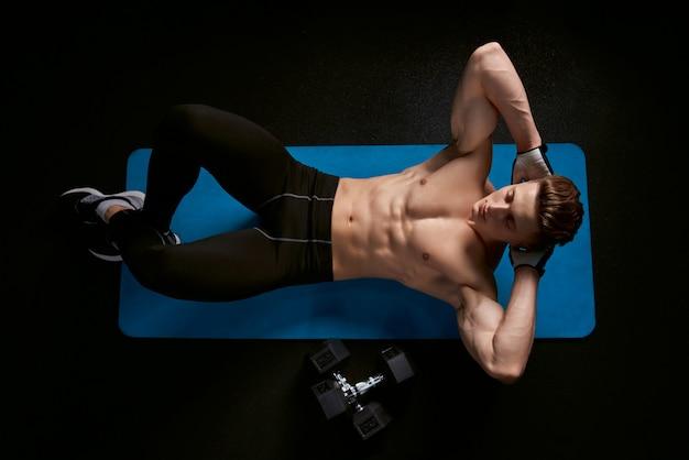 Man doing sit-ups on a mat