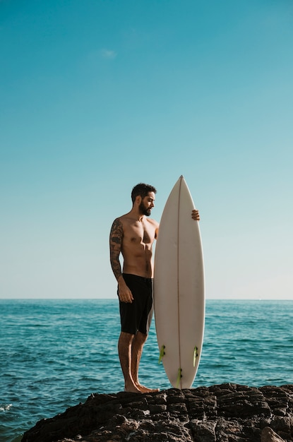 Shirtless man with surfboard standing on rock Free Photo