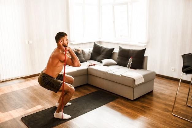 Shirtless man working out at home Premium Photo