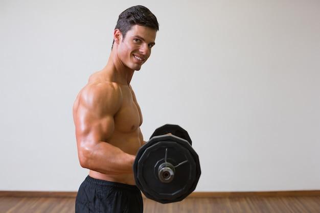 Shirtless muscular man lifting barbell in gym Premium Photo