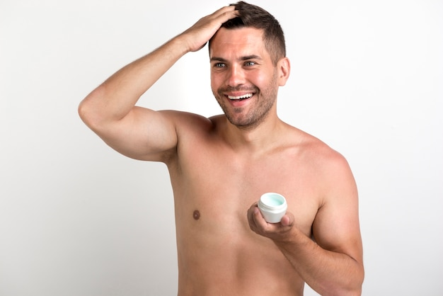 Shirtless smiling man applying wax on his hair against white backdrop Free Photo