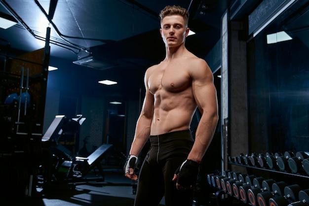 Shirtless sportsman posing in gym. Free Photo