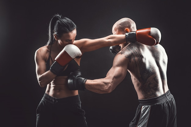 Shirtless woman exercising with trainer at boxing and self defense lesson female and male fight Premium Photo