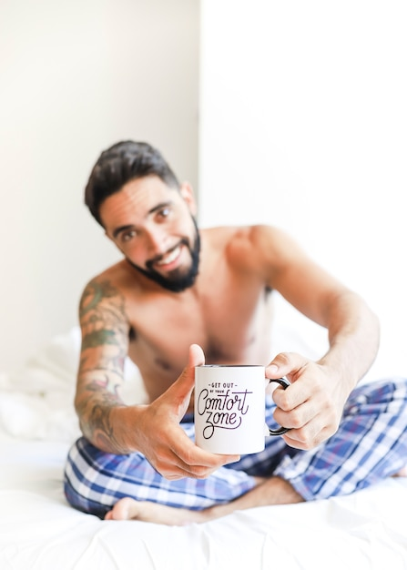 Shirtless young man holding cup of coffee Free Photo