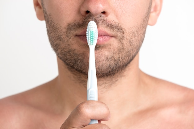 Shirtless young man holding tooth brush in front of his lips Free Photo