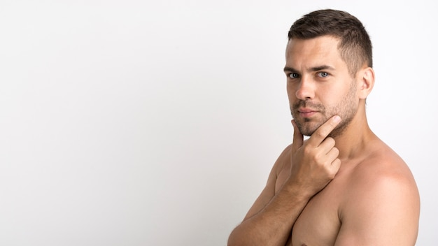 Shirtless young man posing against white background Free Photo