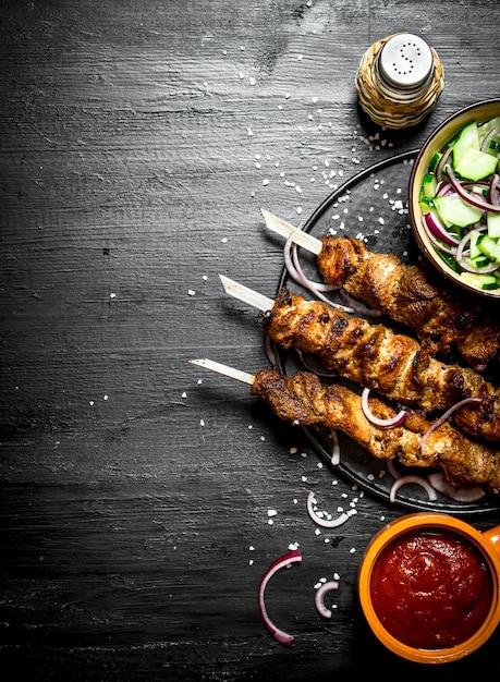 豚肉とサラダのシシカバブ。黒い木製のテーブルの上。 Premium写真