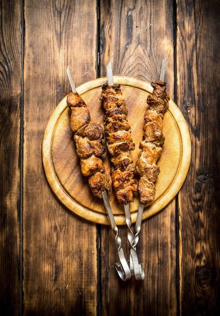 串焼きのシシカバブ。木製の背景に。 Premium写真