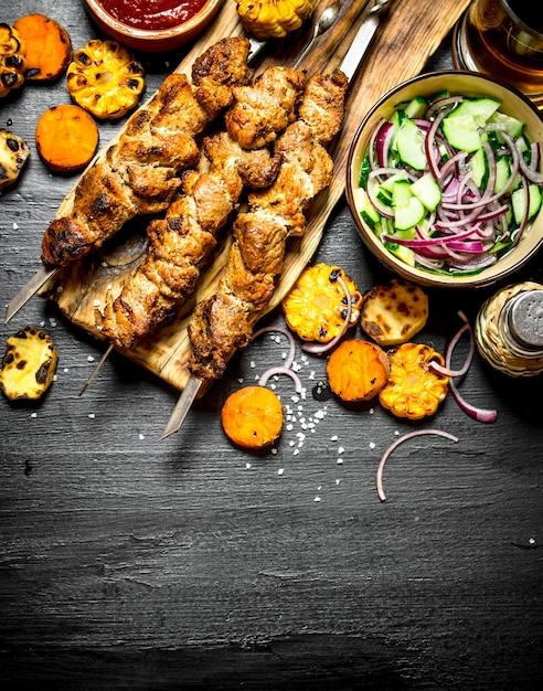 グリル野菜と新鮮なサラダを添えた串焼きのシシカバブ。黒い木製のテーブルの上。 Premium写真