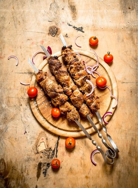 トマトの串焼きにシシカバブ。木製のテーブルの上。 Premium写真