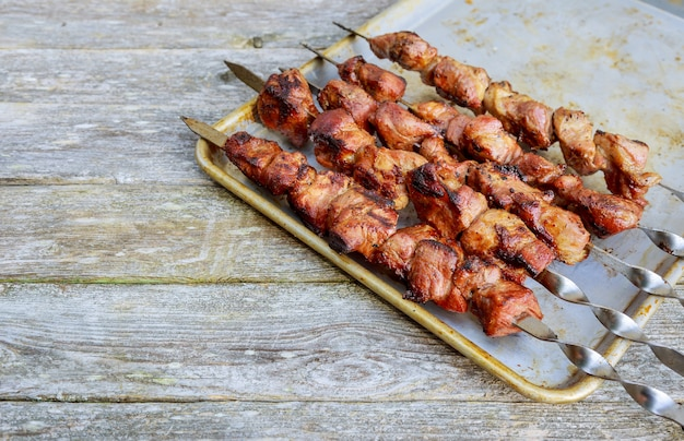 Shish kebab on skewers with onions. on the wooden table. Premium Photo