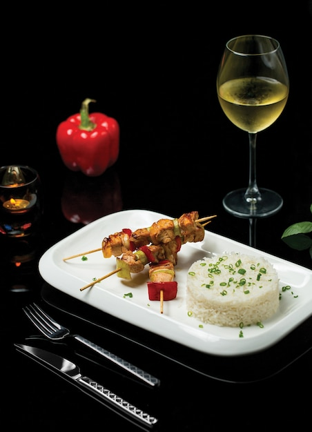 Shish kebab with chicken fillet and rice garnish accompaned by a glass of white wine Free Photo