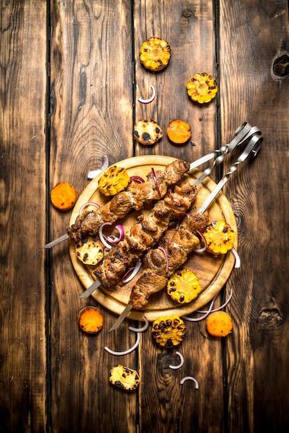 シシカバブと野菜のグリル。木製の背景に。 Premium写真