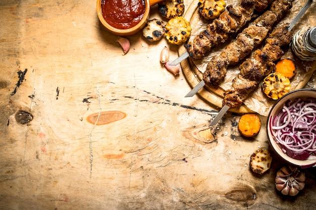 シシカバブのサラダ、野菜、ビール。木製のテーブルの上。 Premium写真