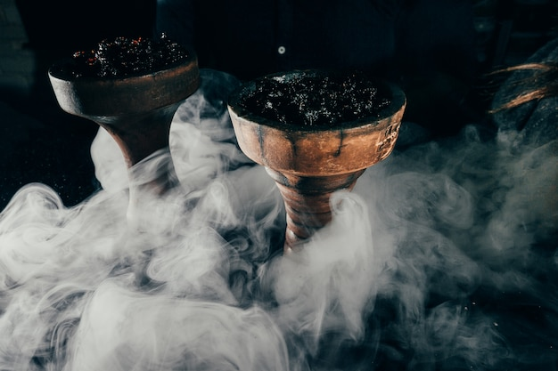 Shisha bowl with craft tobacco and red coal with hookah blue and red smoke background Premium Photo