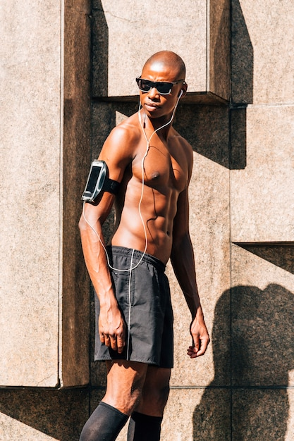 A shitless young muscular man listening music on mobile phone in armband case looking away Free Photo